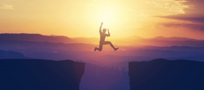 man-jumping-across-cliff